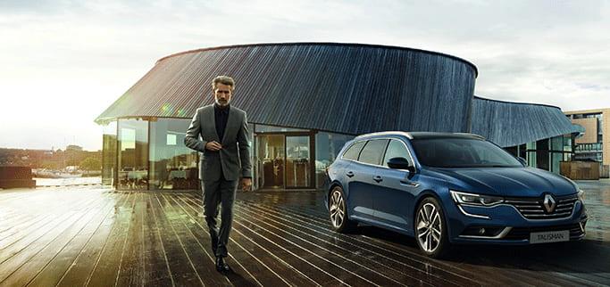 Man i grå kostym passerar en blå Renault Talisman.