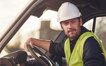 Man med bygghjälm sitter i Renault transportbil